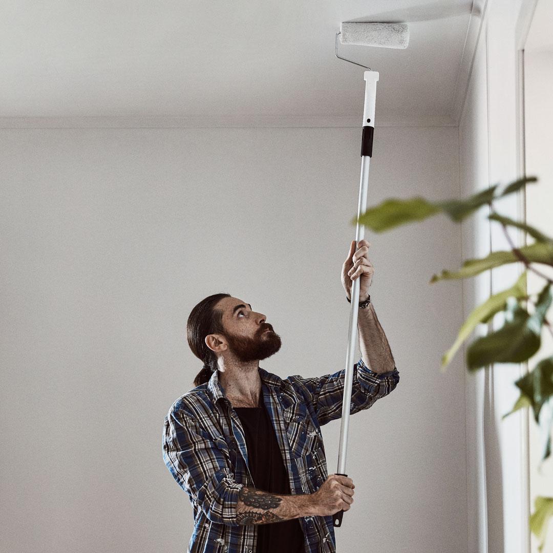man som maler taket hvit med rulle og forlengerskaft