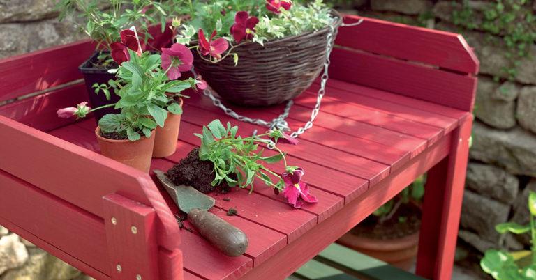 en nymalt rød benk i hagen med planter på toppen