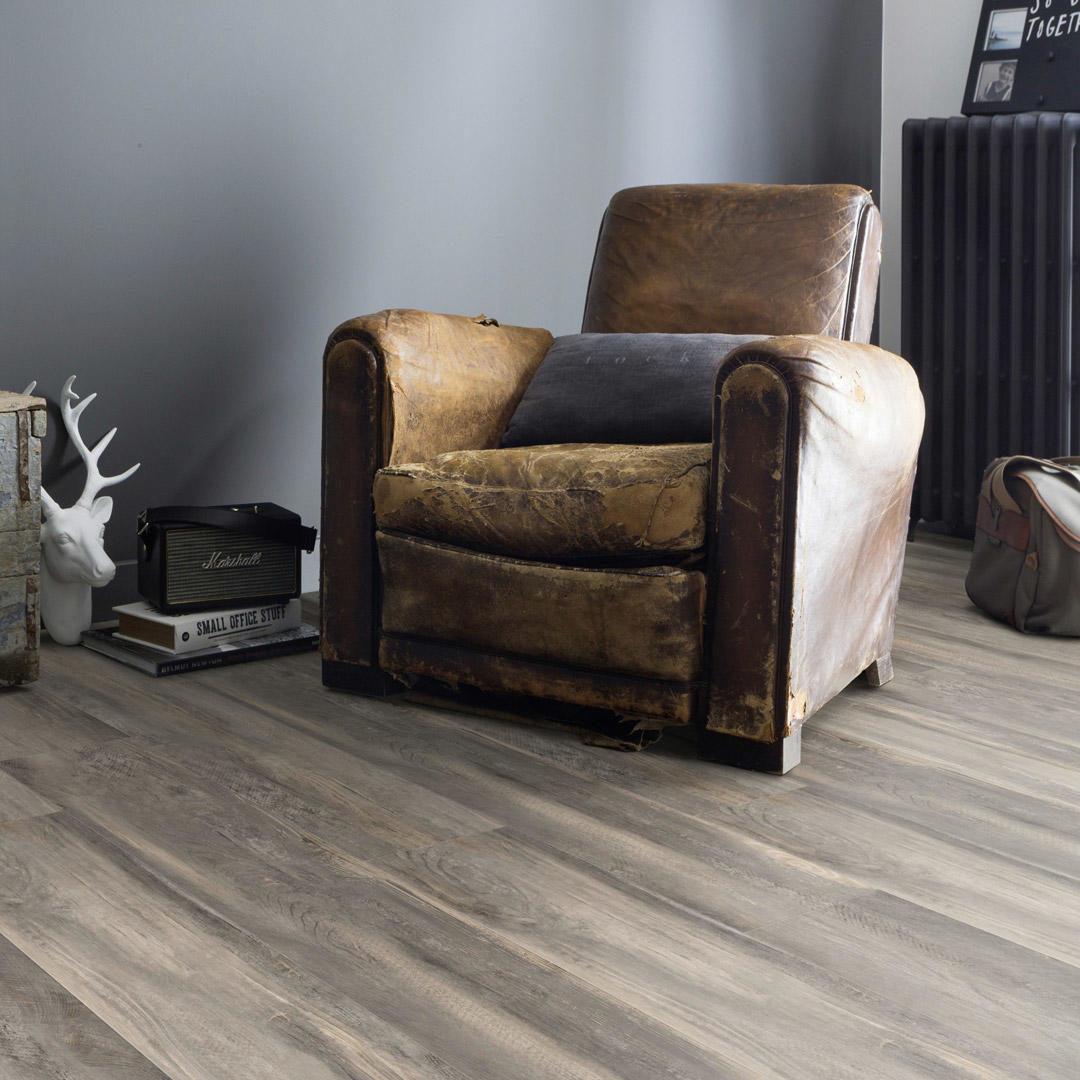 En slitt stol står på gulvet i et rom med blå vegg