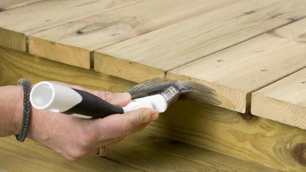 Nærbilde av endetreet på en terrasse som blir beiset med en pensel