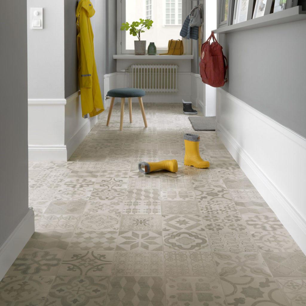 Lys gang med med grått gulv og gule gummistøvler som står midt på gulvet