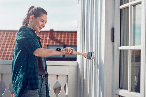 en dame som maler husveggen sin med en langpensel