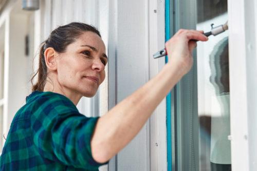 En kvinne maler vinduer hvite
